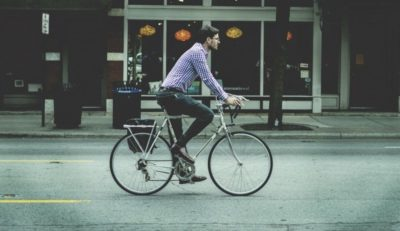 monsieur sur un vélo dans la ville devant un magasin