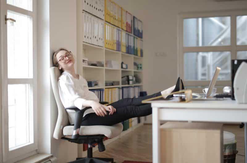 Femme heureuse au travail avec les pieds sur le bureau
