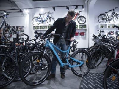 Homme qui essaie un vélo bleu dans un magasin de vélos